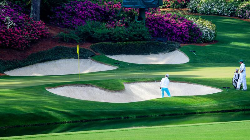 Hudson Swafford plays a stroke from a bunker on the No. 12 hole during Round 1 of the Masters...