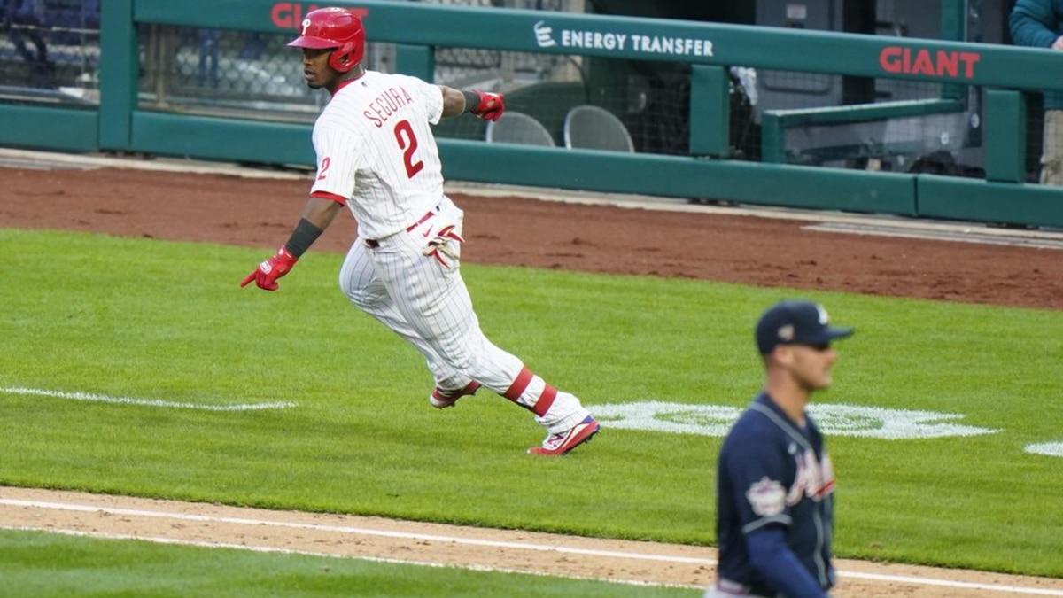 Philadelphia Phillies' Jean Segura, left, reacts after hitting a game-winning RBI-single off...