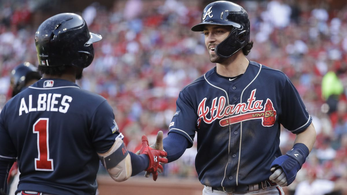 Atlanta Braves' Dansby Swanson, right, celebrates with Ozzie Albies (1) after scoring during the fifth inning in Game 4 of a baseball National League Division Series against the St. Louis Cardinals, Monday, Oct. 7, 2019, in St. Louis. (AP Photo, Charlie Riedel)