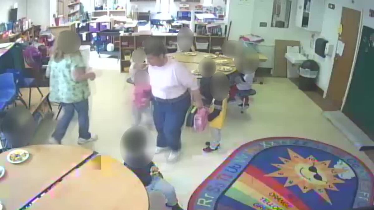 Wendi Nelson, shown here dragging a child from her seat, has been charged with five counts of unlawful conduct toward a child.