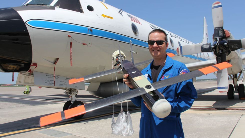 Dr. Cione holds a earlier model of a UAS in front of t P-3 Orion (Source: NOAA)