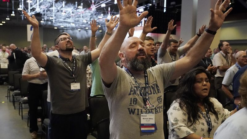 People take part in a worship service during the annual Southern Baptist Convention meeting...
