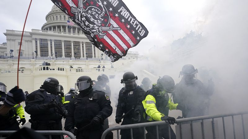 Police hold off Trump supporters who tried to break through a police barrier, Wednesday, Jan....