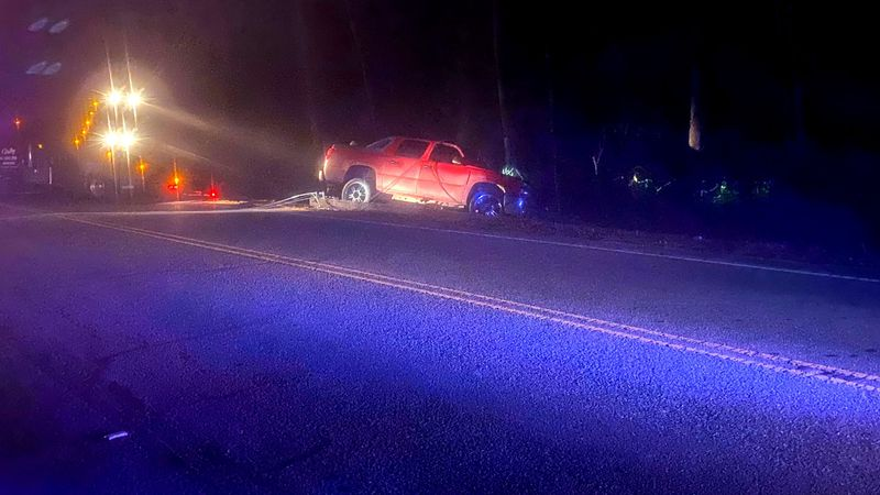 A pickup rests on the shoulder of Augusta Road in Aiken County, where power lines were knocked...