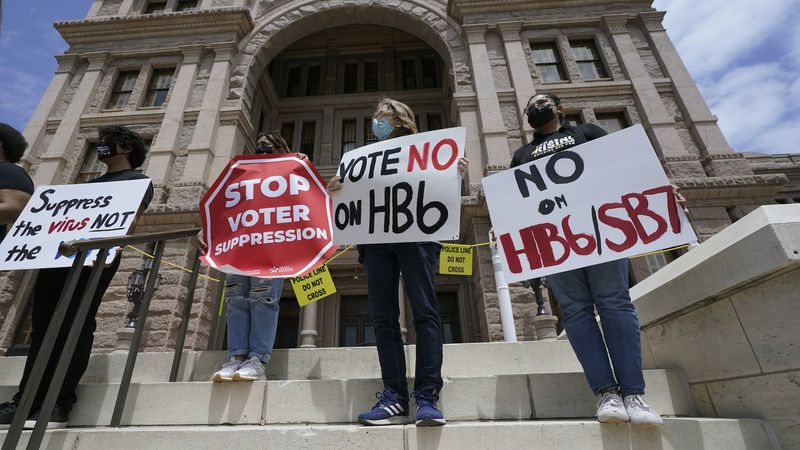 In this April 21, 2021, file photo, people opposed to Texas voter bills HB6 and SB7 hold signs...