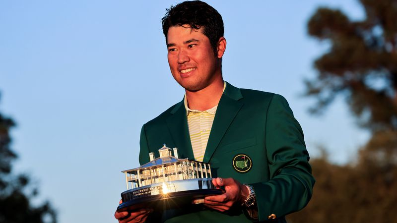 Hideki Matsuyama of Japan is awarded the Masters Trophy and the Green Jacket during the Green...