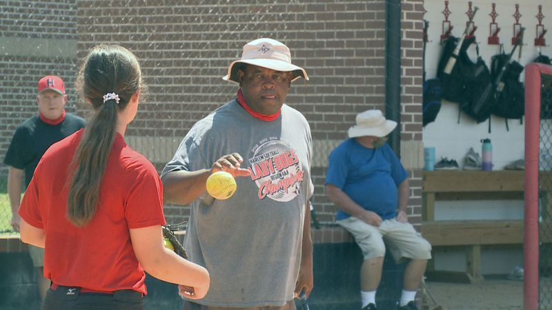 Harlem softball head coach Mike Leverett hits BP in the first practice of the season.