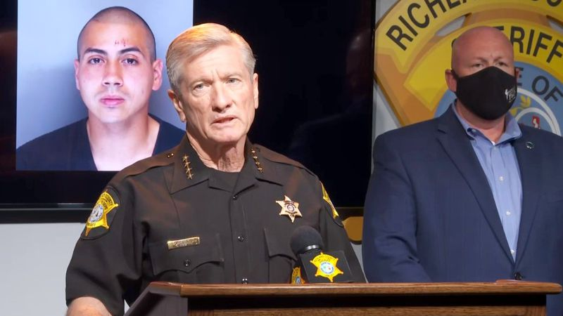 With a photo of the suspect in the background, Richland County Sheriff Leon Lott holds a news...