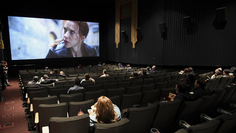 Moviegoers sit in a socially distant seating arrangement at the AMC Lincoln Square 13 theater...