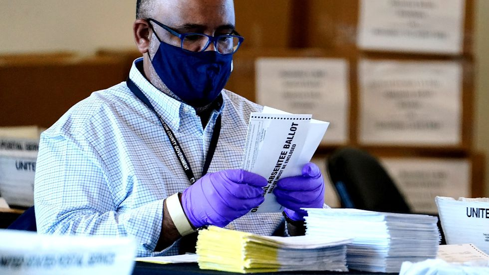 An election inspector looks at an absentee ballot as vote counting in the general election...