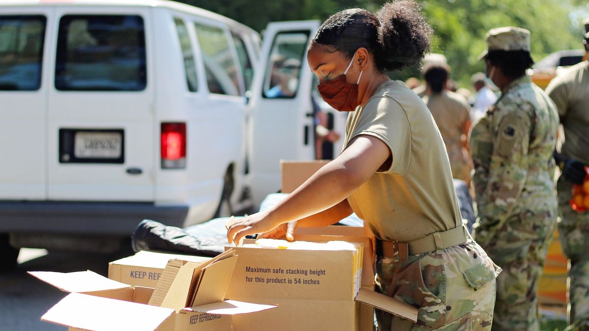 National Guard service members and volunteers from a local food pantry work at a drive-thru,...