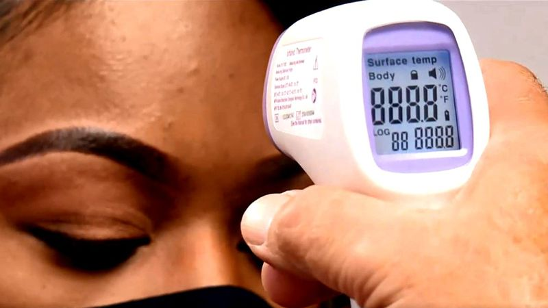 Reporter Tradesha Woodard gets her temperature checked by Augusta University's Dr. Jose Vazquez.