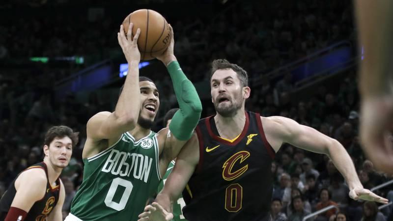 Boston Celtics forward Jayson Tatum (0) drives to the basket next to Cleveland Cavaliers...