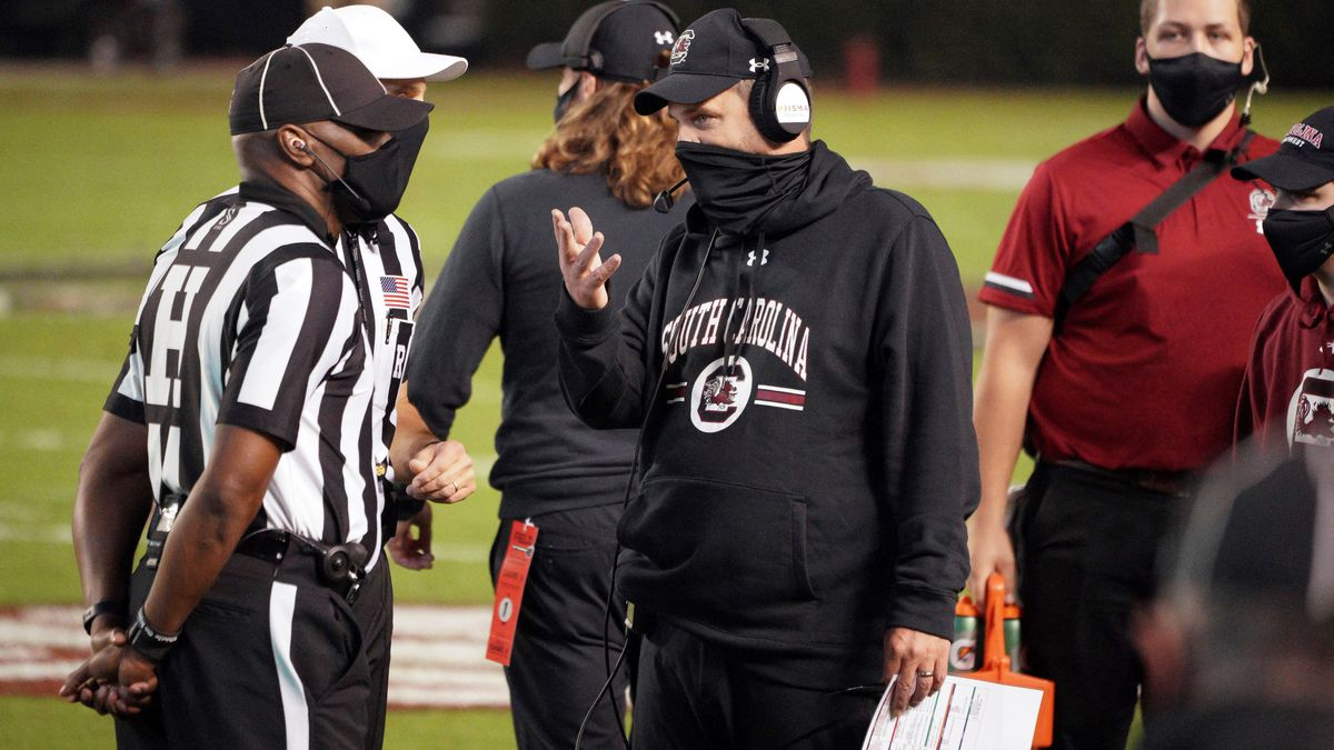 South Carolina interim head coach Mike Bobo walks questions an official during the first half...