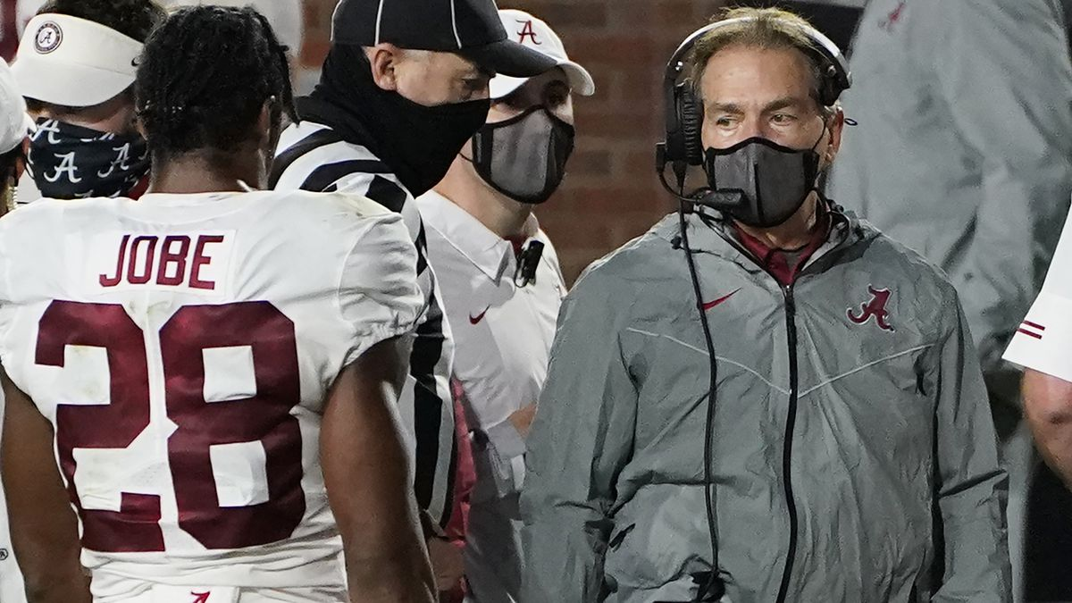 A masked Alabama coach Nick Saban speaks with defensive back Josh Jobe (28) during the second...
