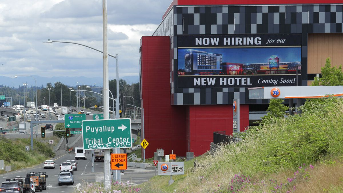 """In this July 9, 2020, file photo, a large video display reads """"Now hiring for our new hotel coming soon!,"""" at the new Emerald Queen Casino, which is open, and owned by the Puyallup Tribe of Indians, in Tacoma, Wash. The number of laid-off workers applying for unemployment aid fell below 1 million for the first time since the pandemic intensified in March, though applications remain at an extraordinarily high level."""