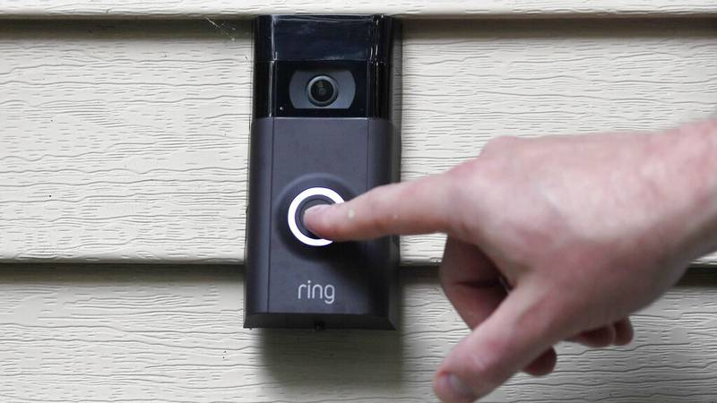 FILE - In this July 16, 2019, file photo, Ernie Field pushes the doorbell on his Ring doorbell...