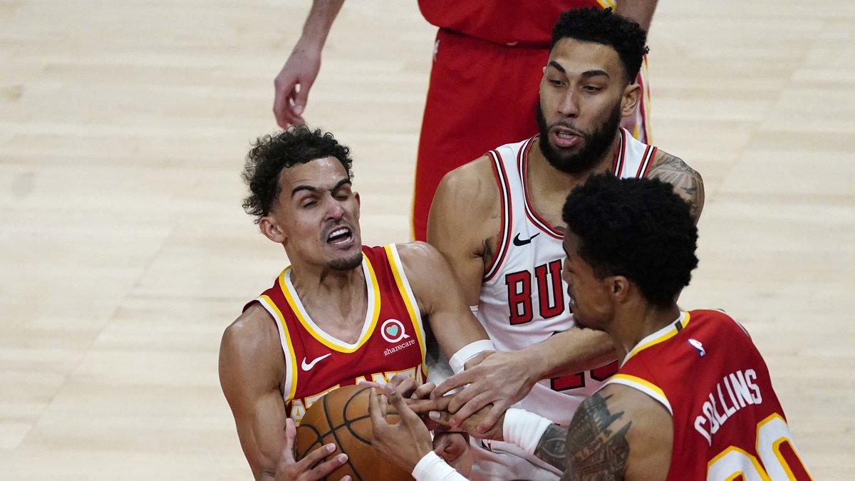 Atlanta Hawks guard Trae Young, left, and John Collins (20) battle Chicago Bulls guard Denzel...
