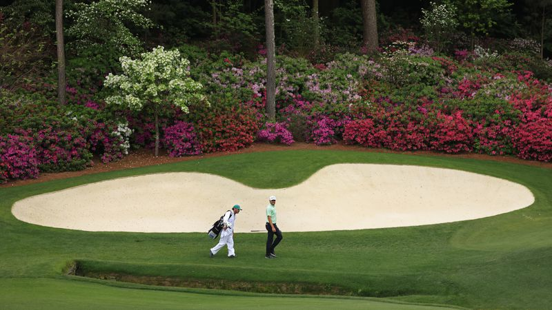 Corey Conners of Canada smiles as he walks to the No. 13 green with caddie Danny Sahl during...