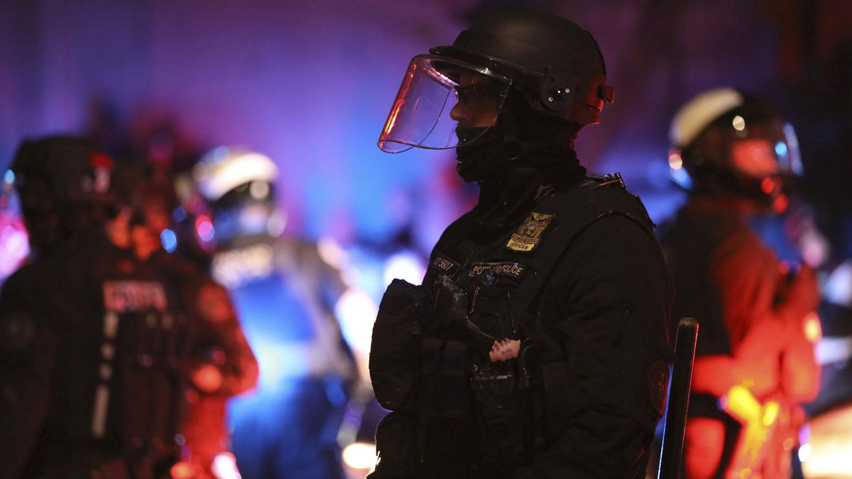 A Portland Police officer watches protesters rallying at the Mark O. Hatfield United States Courthouse on Saturday, Sept. 26, 2020, in Portland, Ore.
