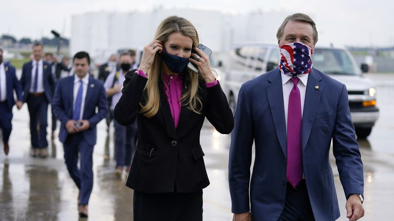 In this July 15, 2020, file photo Sen. Kelly Loeffler, R-Ga., puts on a face mask as she walks...