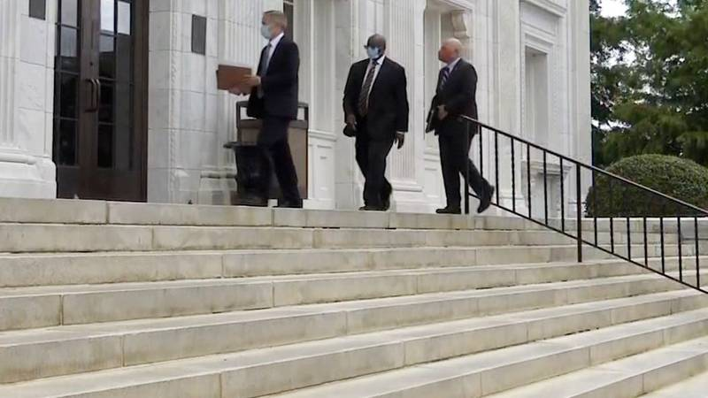 Commissioner Sammie Sias (center) walks into the federal courthouse on Aug. 4, 2021.