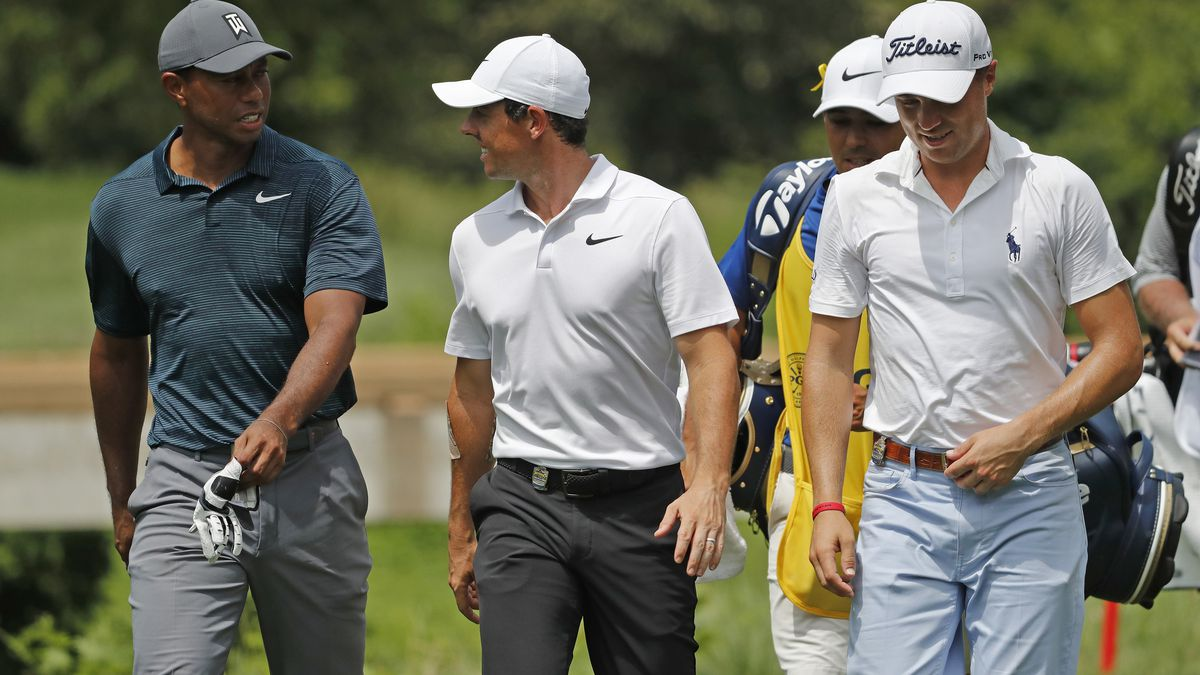 Tiger Woods, left, Rory McIlroy, of Northern Ireland, center, and Justin Thomas, right, walk...