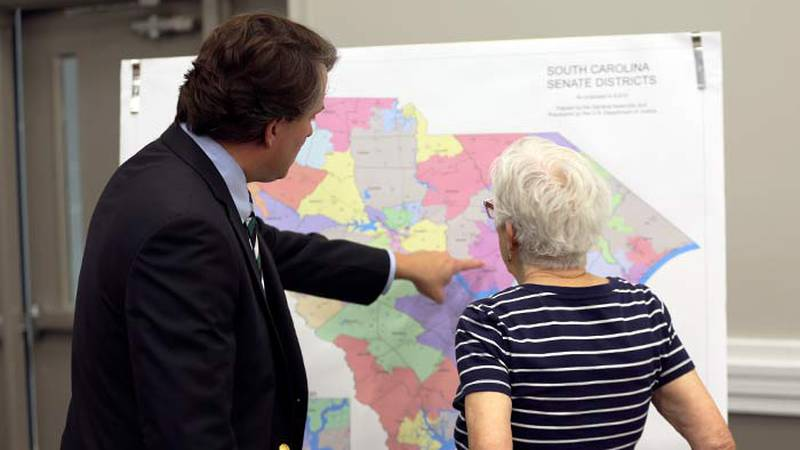 People look over the current South Carolina Senate districts at a public meeting by a Senate...