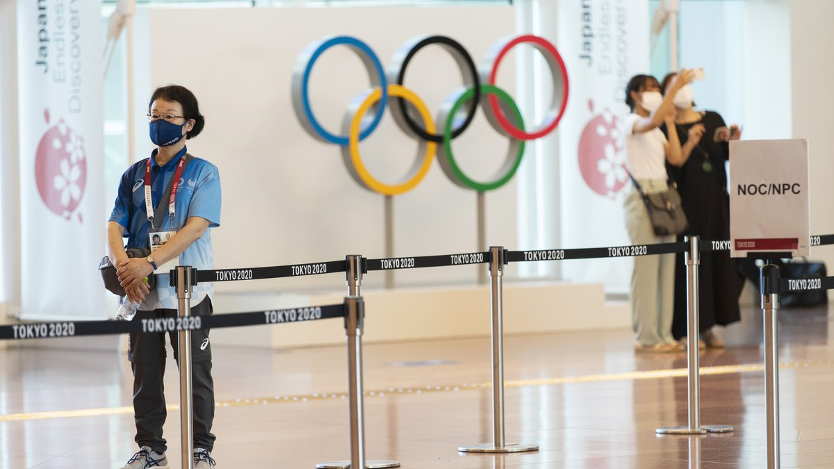 A Tokyo 2020 staff member stands by to help direct team members from other countries for the...