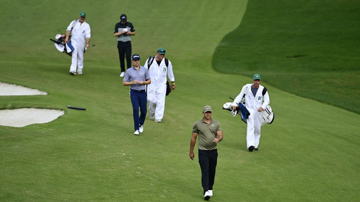 Brooks Koepka, Justin Thomas, and Matthew Fitzpatrick of England walk up the fairway on the No....