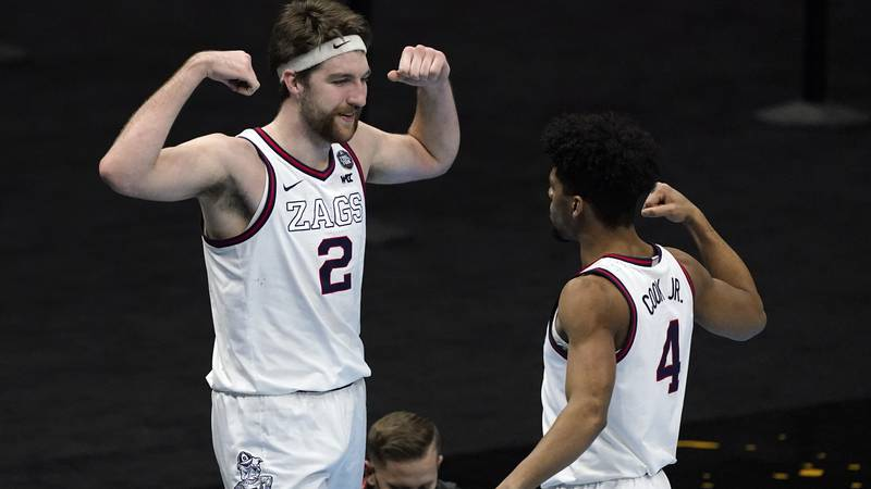 Gonzaga forward Drew Timme (2) celebrates with teammate guard Aaron Cook (4) after making a...