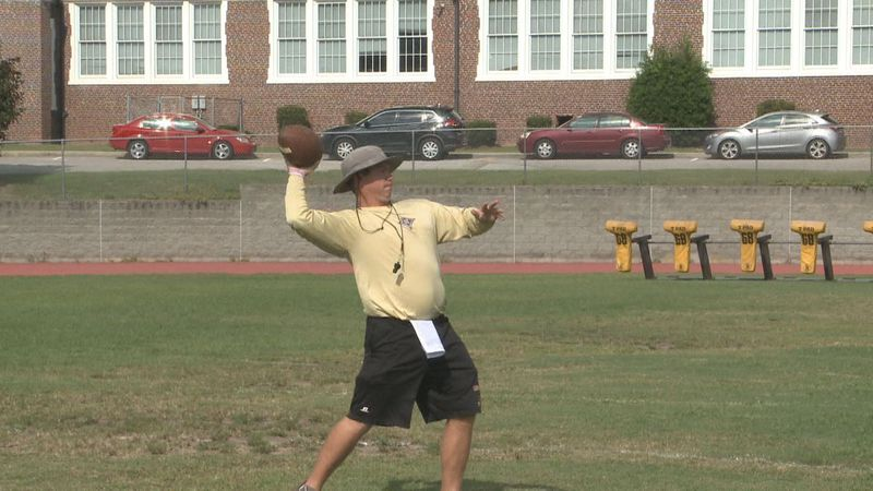 Head coach Lyle Burns works with defensive backs during football practice.