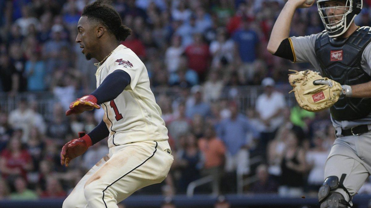 Atlanta Braves' Ozzie Albies (1) tries to avoid a tag as Pittsburgh Pirates catcher Jacob...