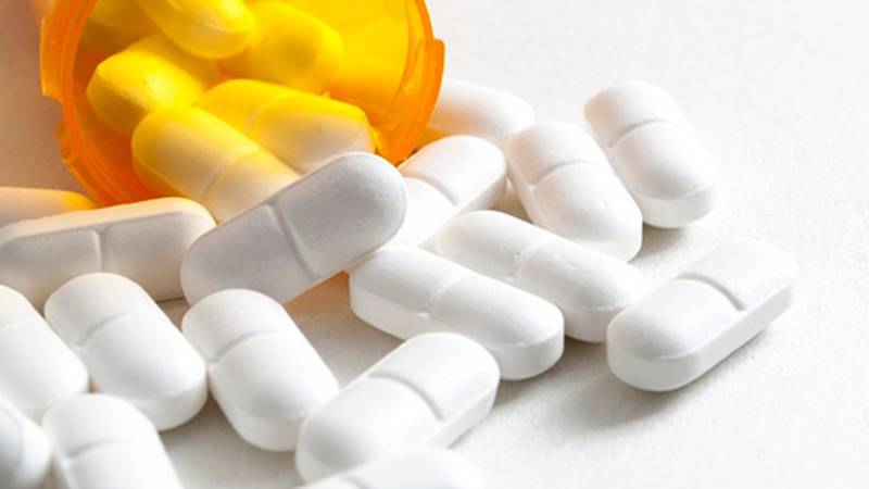 Opioid epidemic, drug abuse and overdose concept with scattered prescription opioids spilling...