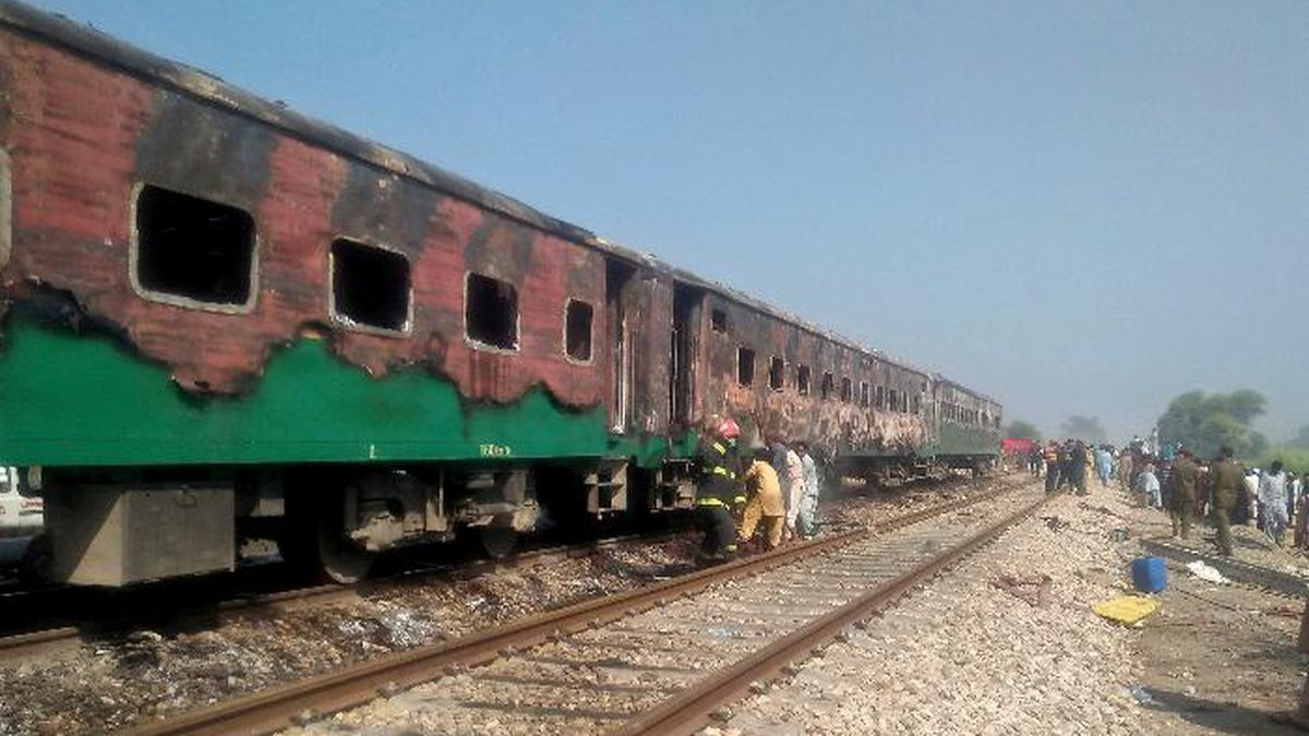 Pakistani officials examine a train damaged by a fire in Liaquatpur, Pakistan, Thursday, Oct....